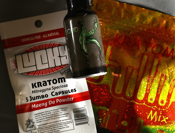 A bottle with Kratom liquid and bags of capsules with the herbal supplement Kratom inside.