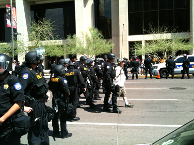 A man is escorted away from a scene by police in downtown Phoenix during demonstrations over Arizona's controversial immigration law on Thursday, July 29, 2010. About two dozen SB1070 opponents refused to disperse after Phoenix police declared an unlawful assembly. Police began arresting protesters at 11:50 a.m. The arrests were peaceful.