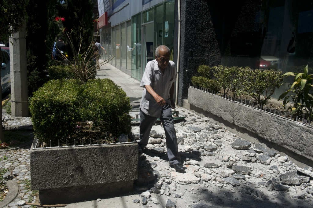 A man walks over the debris fell from a building in Mexico City damaged during a strong quake that hit Mexico on March 20, 2012.