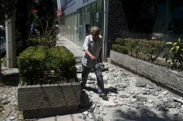 A man walks over the debris fell from a building in Mexico City damaged ...