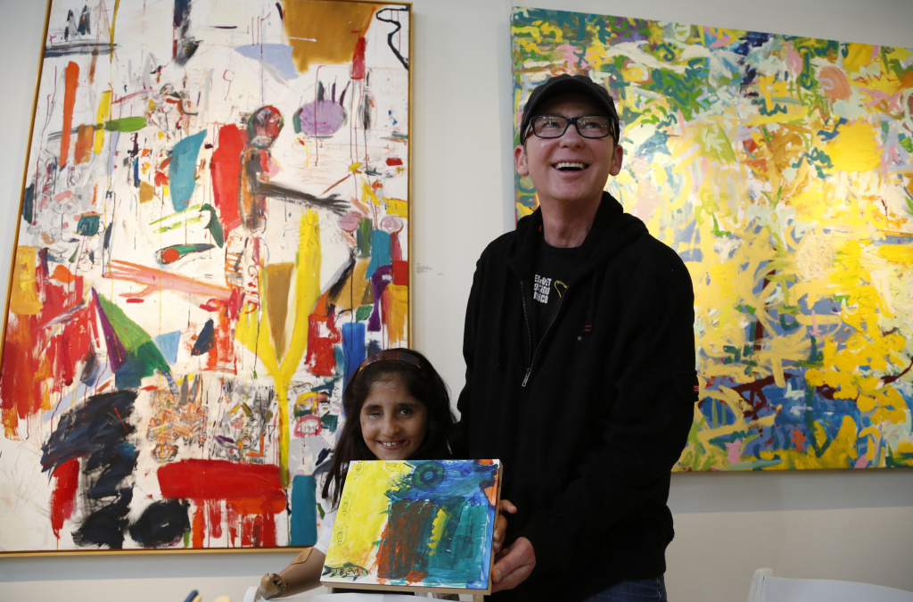Afghan war victim Shah Bibi Tarakhail, left, smiles as she shows her own painting with artist Dayvd Whaley.