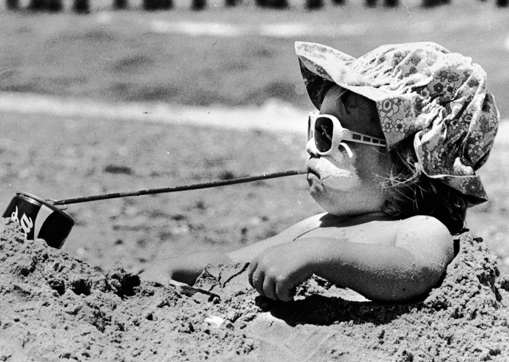 File photo: Danielle Martin enjoying a cold drink as she sits in a sand hole on the beach near Melbourne.