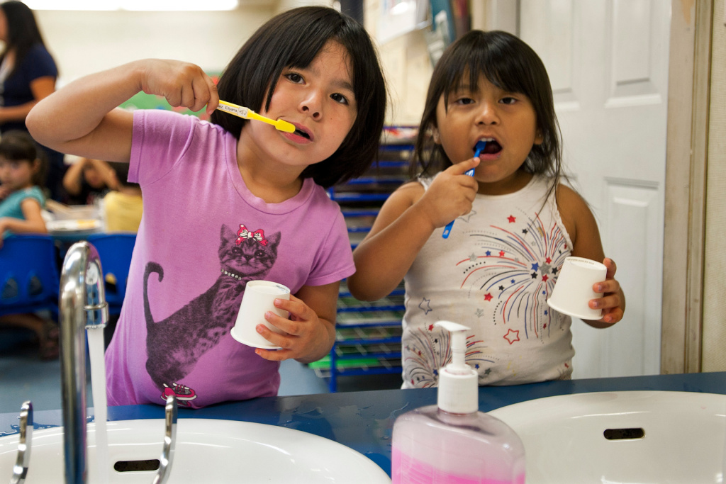 Ellyana Benitez, left, and Briana Melgar brush their teeth after lunch. The program the children attend, Options in Monrovia, was one of the first to feel the sequestration cuts losing the afternoon class.