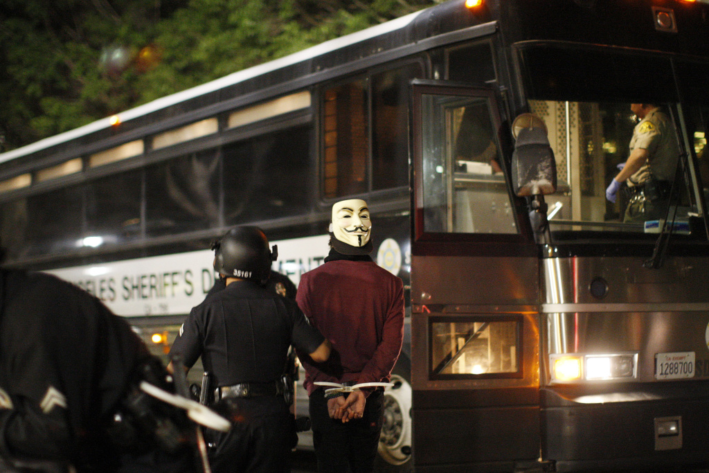 n arrested protester is lead onto a Los Angles Police Departmet (LAPD) transport bus at one intersection during a demonstration following the grand jury decision not to indict a white police officer who had shot dead an unarmed black teenager in Ferguson, Missouri in the early morning hours of November 26, 2014 in Los Angeles, California.
