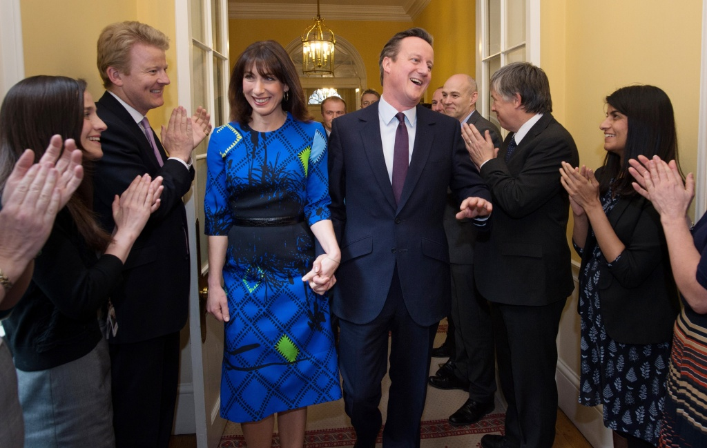 Britain's Prime Minister and Leader of the Conservative Party David Cameron and his wife Samantha are applauded by staff upon entering 10 Downing Street in London on May 8, 2015, after visiting Queen Elizabeth II, a day after the British general election.