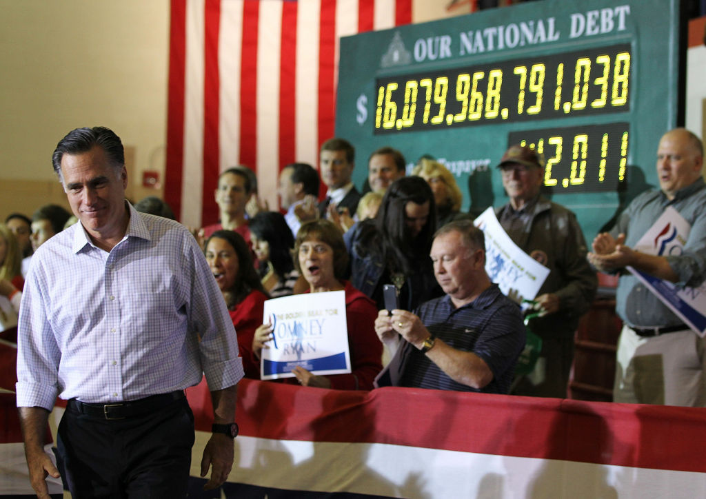 Republican U.S. presidential candidate Mitt Romney arrives at a campaign rally at Westerville South High School as a national debt clock runs in the background September 26, 2012 in Westerville, Ohio. Romney continued his two-day