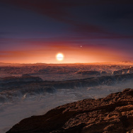 An artist's depiction of the surface of the planet Proxima b as it orbits the red dwarf star Proxima Centauri, the closest star to our solar system. The planet is a bit more massive than Earth, scientists say, and circles its star once every 11 days.