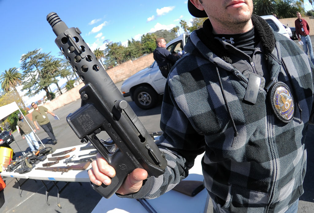 In this file photo, an LAPD officer holds a collected assault weapon during the Gun Buyback Program event in the Van Nuys area of north Los Angeles on December 26, 2012. On Tuesday, a California Senate committee approved seven different gun-control measures, including two with new restrictions on semi-automatic rifles.