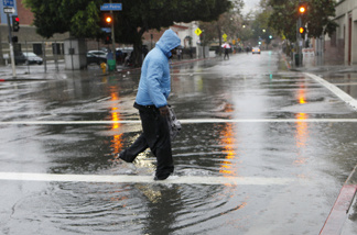 A pedestrian walks through a flooded gutter in Los Angeles, Monday, Dec. 20, 2010.