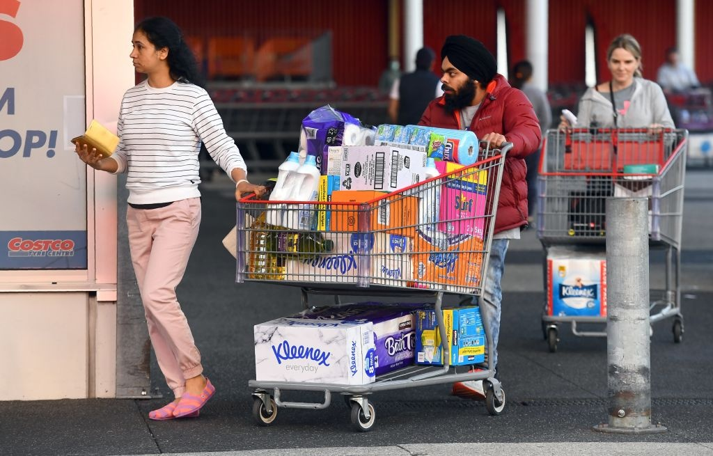 People leave a Costco outlet with a trolley full of toilet paper and cleaning products as fears of a second wave of COVID-19 have sparked a rush on some supermarket items in Melbourne on June 24, 2020.