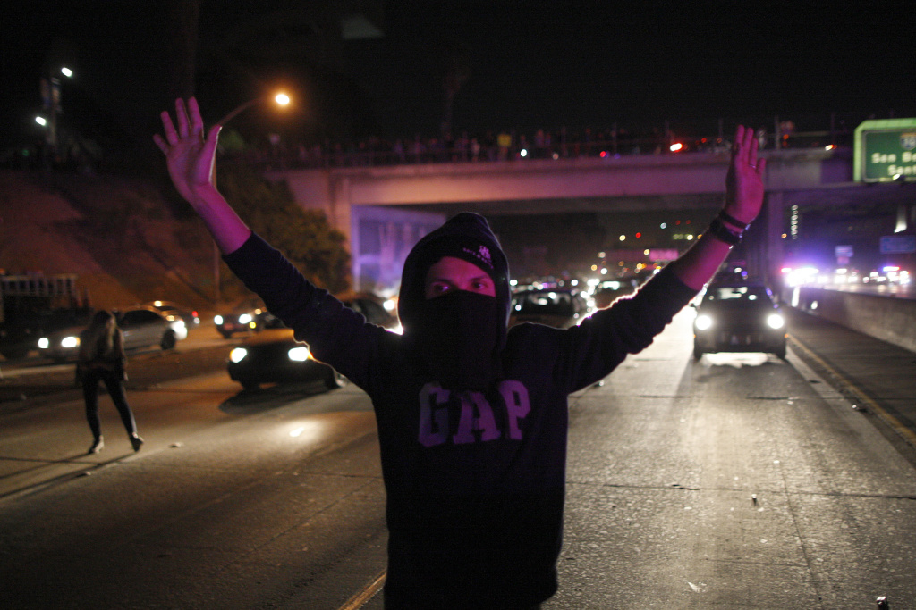 A man is illuminated by the lights of approaching police vehicles as protesters set up barricades and shut down the 101 freeway following the grand jury decision not to indict a white police officer who had shot dead an unarmed black teenager in Ferguson, Missouri on the night of Nov. 25, 2014 in Los Angeles.