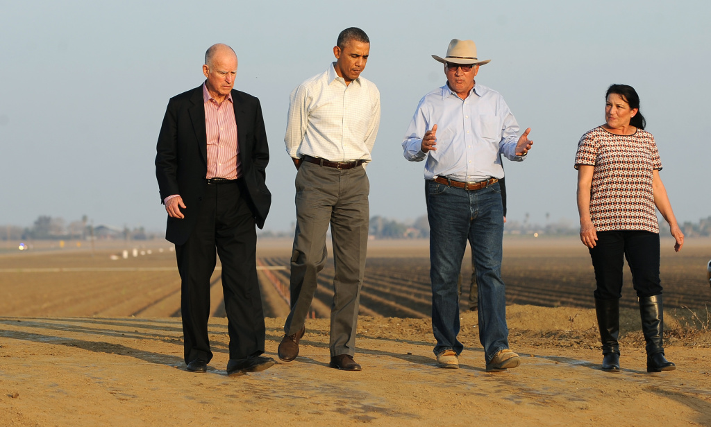 US President Barack Obama (2nd-L) walks with California Governor Jerry Brown (L), Joe and Maria Del Bosque (R) of Empresas Del Bosque farm, addressing California's drought situation Friday, Feburary 14, 2014 in Los Banos, CA.