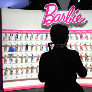A woman photographs a wall of Barbie dolls