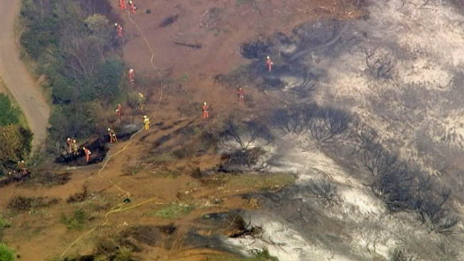 A Los Angeles County Fire Department helicopter drops water on a fire burning on the foothills of the San Gabriel Mountains in Monrovia, Calif., on Saturday, April 20, 2013.