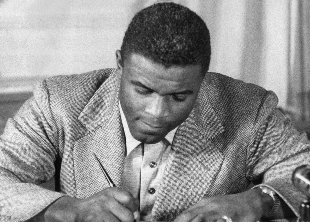 File: Undated photo of US baseball star Jackie Robinson as he signs a then-record contract to play for the Brooklyn Dodgers.