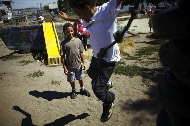 Deion Jefferson, 10, and Samuel Jefferson, 7, take turns climbing and jumping off a stack of old tires at the Berkeley Adventure Playground in California. The playground is a half-acre park with a junkyard feel where kids are encouraged to