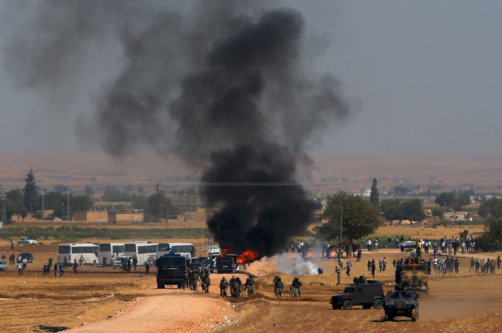 A car hit by a teargas canister burns as riot police use teargas to disperse Kurdish demonstrators as thousands of Syrian refugees continue to arrive at the border in Suruc, Turkey, Monday, Sept. 22, 2014. A new tracking system has found that nearly one in five ammunition cartridges found on Islamic State fighters were actually made in the US.