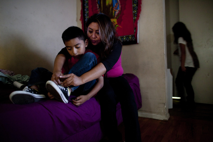 Claudia Chi Ku helps her son, Johnny Ramirez, 7, tie his shoes before leaving their apartment in Pico Union. Chi Ku has lived in the apartment with her four children for three years. She works are a cashier at a restaurant nearby.