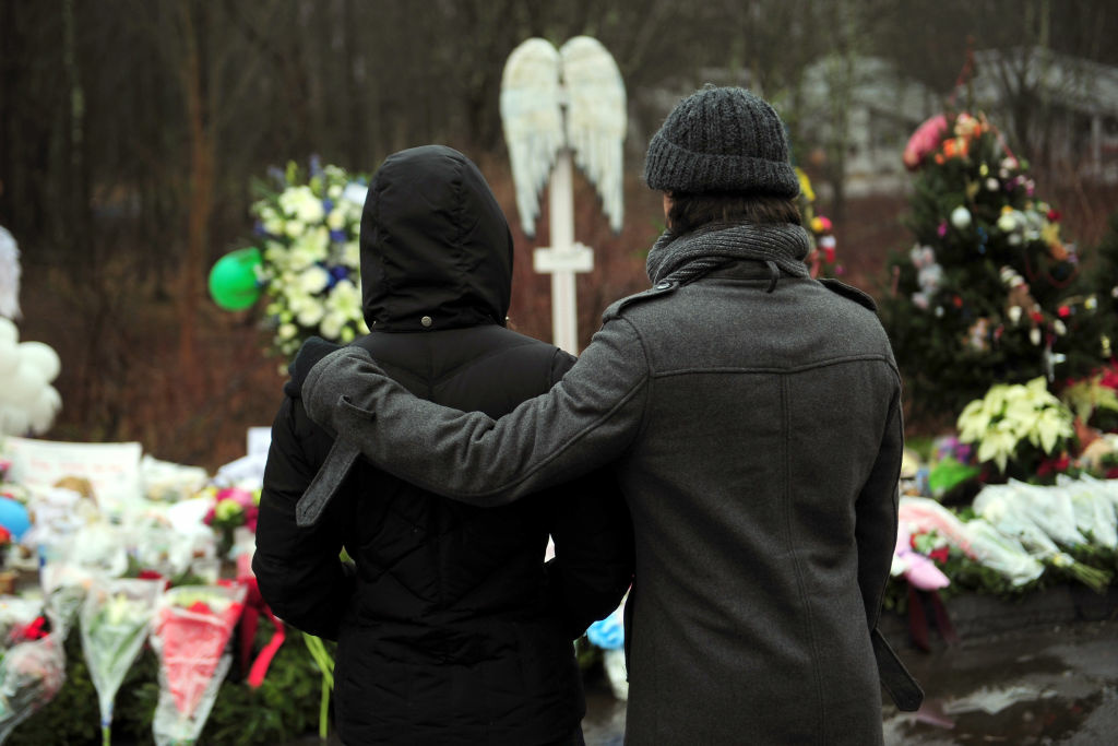 People pay their respects at a makeshift shrine to the victims of an elementary school shooting in Newtown, Connecticut, December 17, 2012.