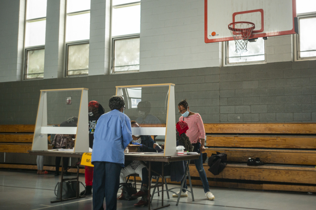 Poll workers sit behind plexiglass barriers during primary elections on June 2, 2020 in Philadelphia. Many cities are reporting a surge of volunteers to work the polls although Philadelphia still faces a shortage ahead of next month's election.