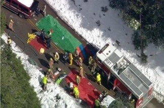 This video image provided by CBS2/KCAL9 News shows rescue efforts after a school bus carrying up to 25 children aboard slid over the side of a highway in a Southern California ski area near Twin Peaks, Calif., after colliding with a Nissan Murano traveling the opposite direction.
