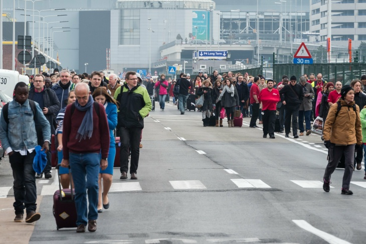 People react as they walk away from Brussels airport after explosions rocked the facility in Brussels, Belgium Tuesday March 22, 2016.   Explosions rocked the Brussels airport and the subway system Tuesday, just days after the main suspect in the November Paris attacks was arrested in the city, police said.