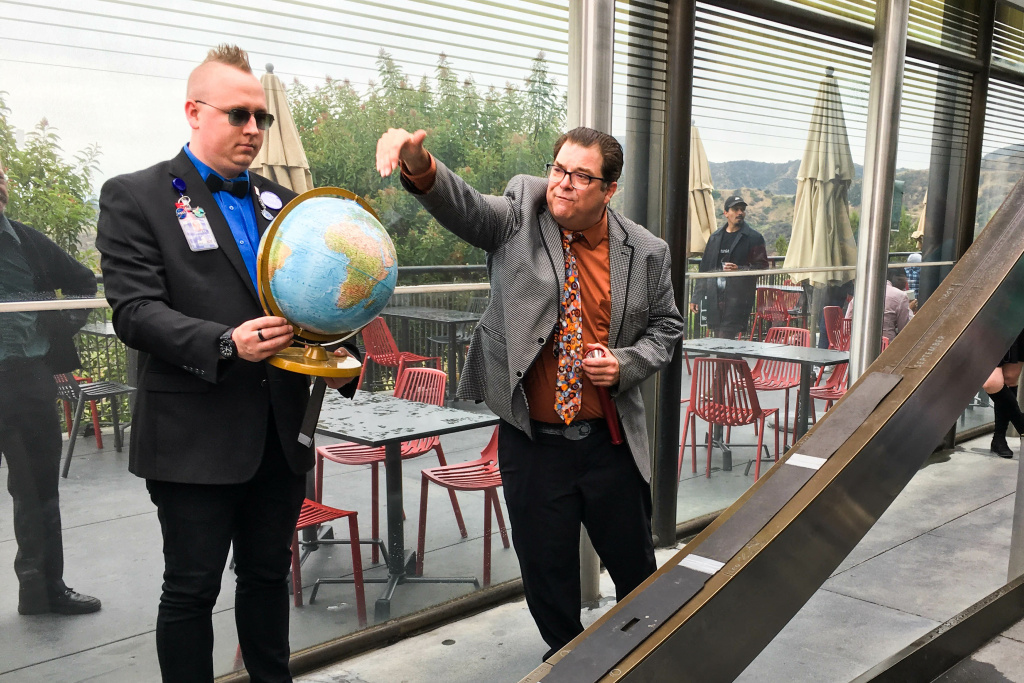 Griffith Park Observatory docent Jared Head (left) and astronomer David Reitzel (right) use a globe to explain the summer solstice.