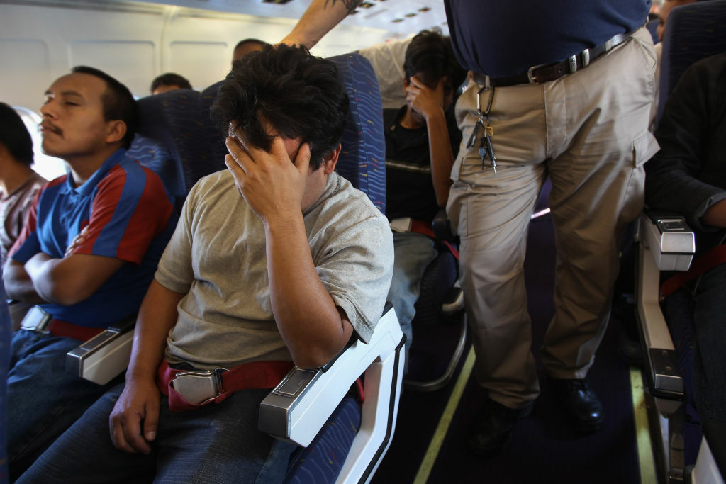 Guatemalan immigrants are supervised by guards while on a deportation flight from Mesa, Arizona on June 24, 2011 in flight to Guatemala City. Federal officials are expected to announce year-end fiscal year 2013 deportation numbers on Thursday; preliminary numbers suggest a slowdown in removal this year, at least from last year's record high.