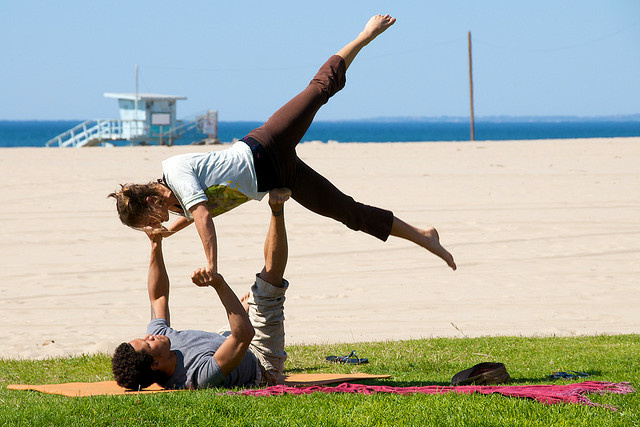 A couple does a yoga workout on the beach in Los Angeles.