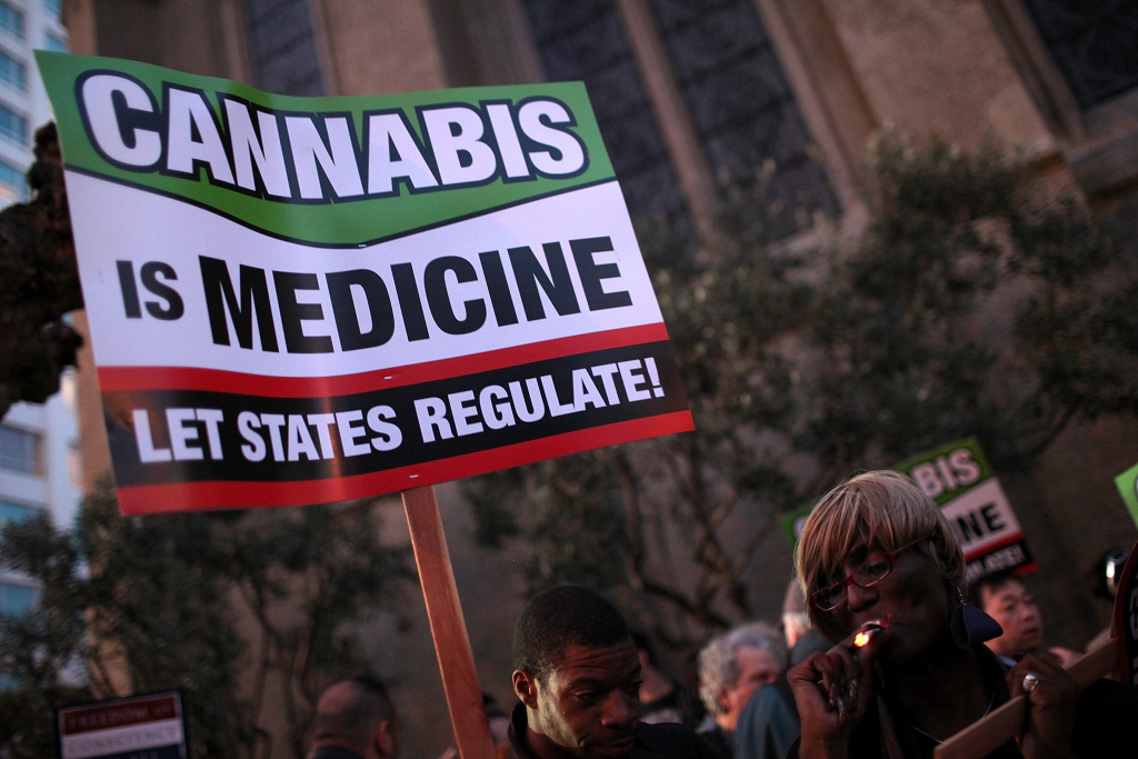Medical marijuana advocates hold signs as they demonstrate outside the site where U.S. President Barack Obama was holding a fundraiser on February 16, 2012 in San Francisco, California.
