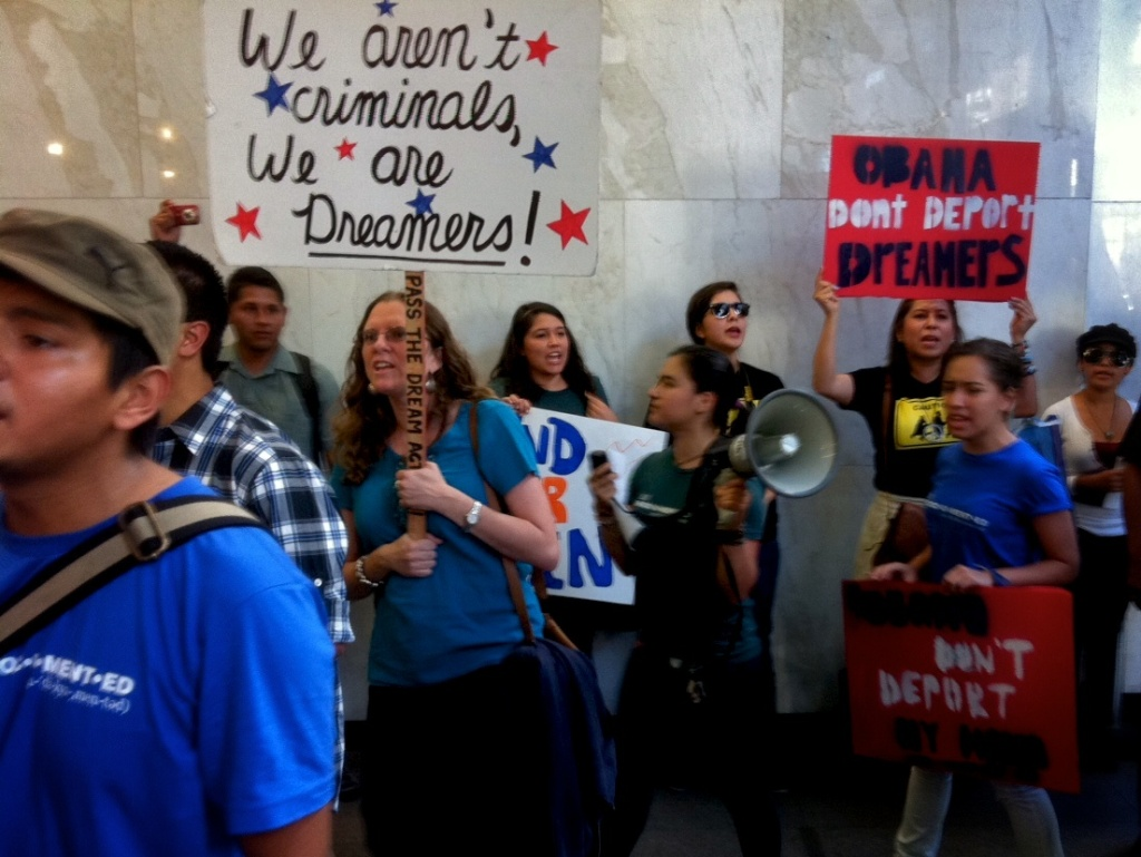 Over 50 protesters march in the lobby of the Immigration Court building.