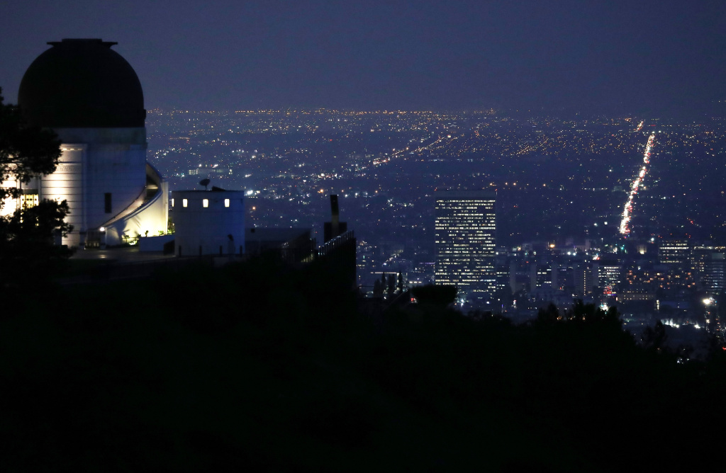 The Griffith Observatory (L) stands above downtown on April 2, 2018 in Los Angeles, California.