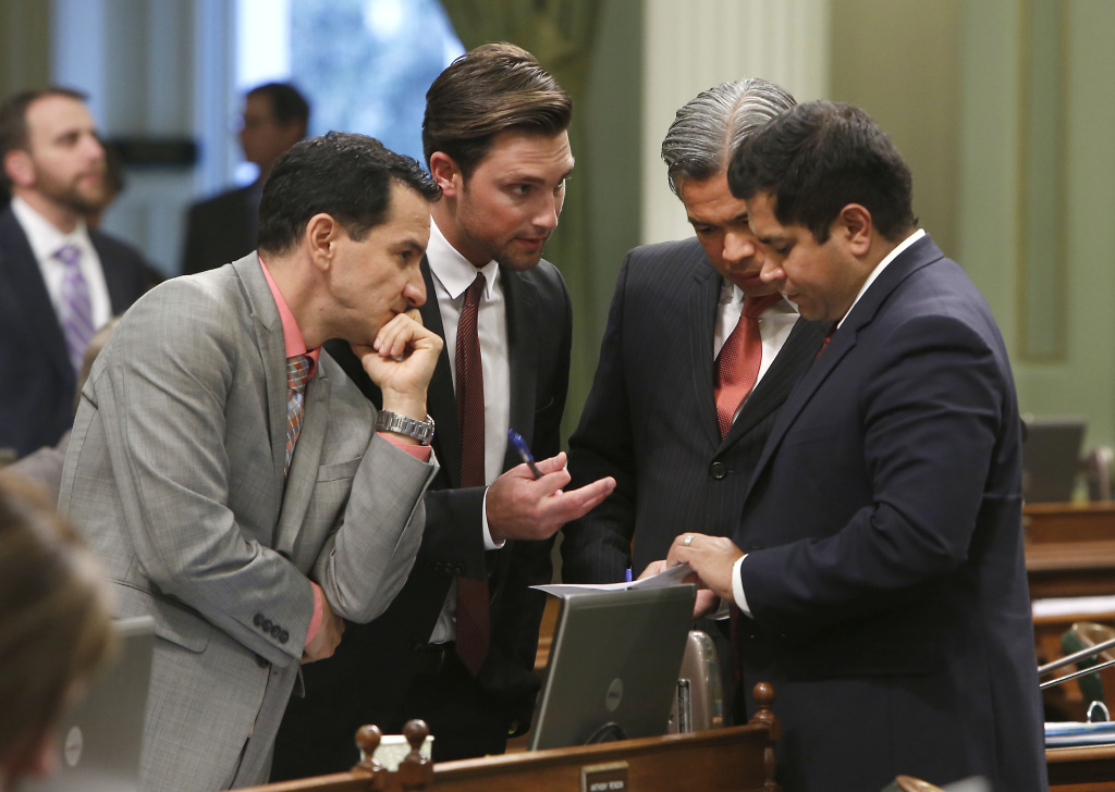 Assemblyman Jimmy Gomez of Los Angeles huddles with other Democratic lawmakers during a session at the Capitol in Sacramento, Calif., in this September 2013 file photo. Gomez introduced a bill Wednesday to help high schools teach students to tell real news from fake.