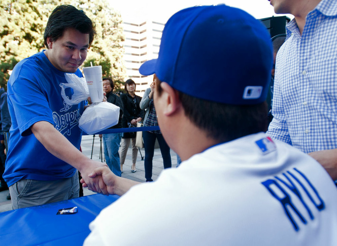 Hyun-Jin Ryu, the Dodgers' newest pitcher, signs a ball for life-long fan Joe Hiraga of Monterey Park on Tuesday outside the Radio Korea building.