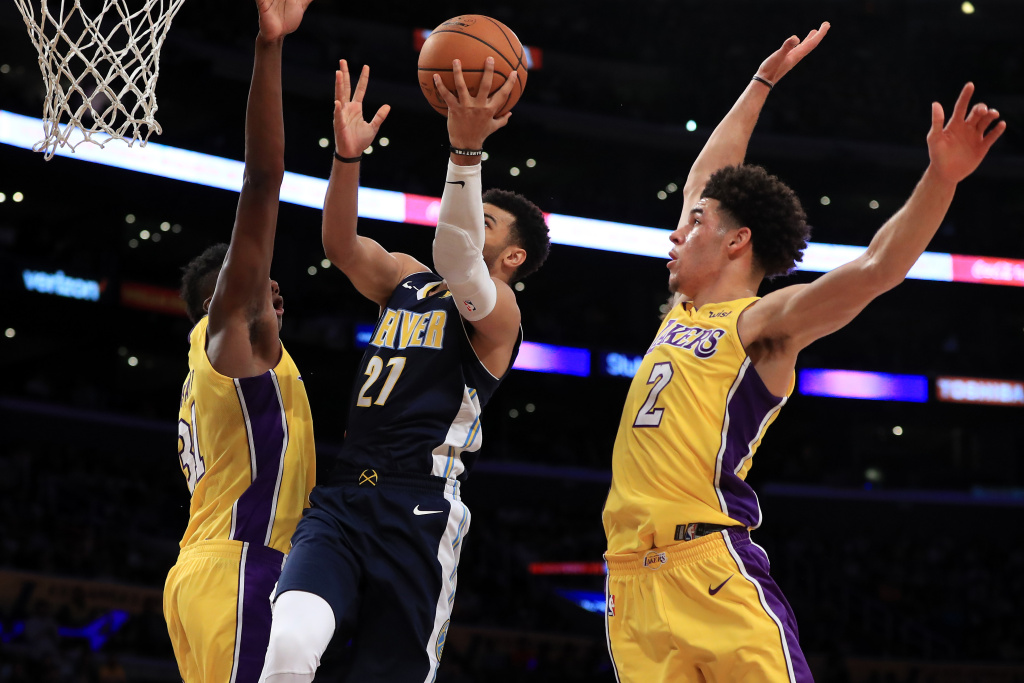 Wilson Chandler #21 of the Denver Nuggets splits the defense of Lonzo Ball #2 and Thomas Bryant #31 of the Los Angeles Lakers during the second half of a preseason game at Staples Center on October 2, 2017 in Los Angeles, California.