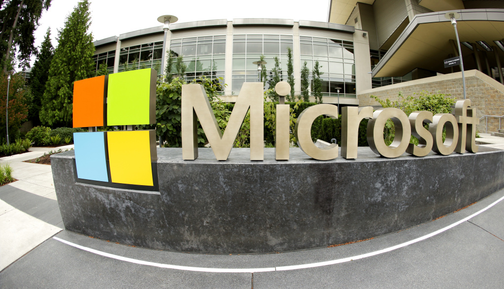 This photo taken with a fisheye lens on July 3, 2014 shows Microsoft Corp. signage outside the Microsoft Visitor Center in Redmond, Wash. Microsoft on Thursday, July 17, 2014 announced it will lay off up to 18,000 workers over the next year.