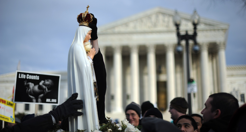 A marcher places a crown atop a statue of the Virgin Mary as she is carried in front of the U.S. Supreme Court during the March for Life on January 24, 2011, on Capitol Hill in Washington, DC.
