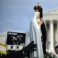 A marcher places a crown atop a statue o