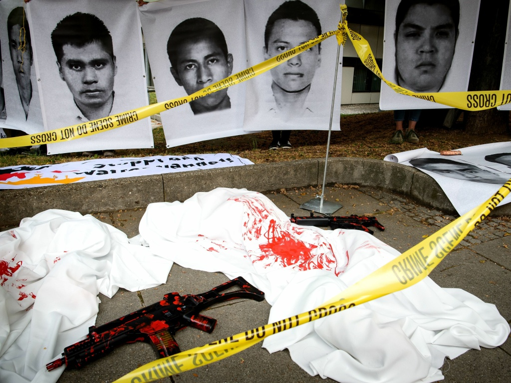 German demonstrators used crime scene tape and replica guns to draw attention to a trial over Heckler & Koch's deal that sent G36 rifles to several Mexican states that were under a ban. The company was ordered to pay a large fine on Thursday. The photos above show images of Mexican students believed to have been killed with the weapons.