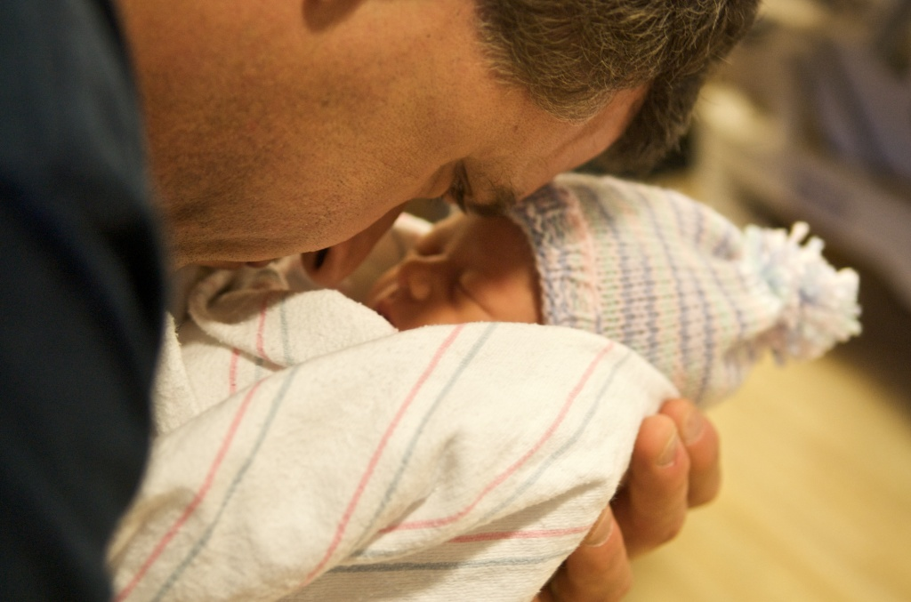A father cradles his newborn baby.