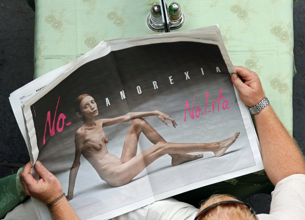 A man reads an Italian newspaper showing the new fashion brand Nolita's advertising campaign against anorexia, realized by Oliviero Toscani