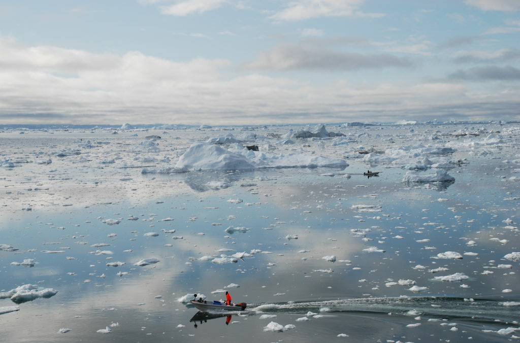 A picture taken on July 3, 2009 shows a fisherman sailing on the Ice Fjord of Ilulissat in Greenland. The Greenland ice sheet has lost 1,500 billion tonnes of ice since 2000, contributing 0.75 mm (0.03 inch) annually to sea levels, according to a study published in December 2009. Some experts believe the Arctic ice cap will disappear completely in summer months within 20 to 30 years.
