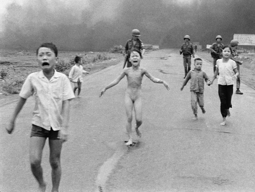 This is a June 8, 1972, photo of South Vietnamese forces following after terrified children, including 9-year-old Kim Phuc, center, as they run down Route 1 near Trang Bang after an aerial napalm attack on suspected Viet Cong hiding places.