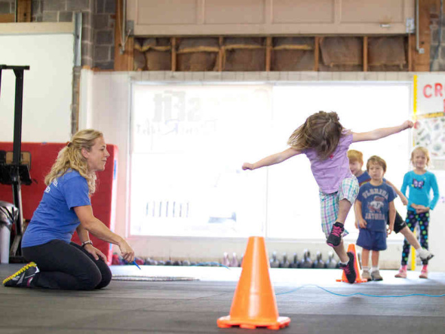 Six-year-old Rose MacDermott (front) lifts a barbell as part of a CrossFit class for children at CrossFit DoneRight in Rockville, Md.