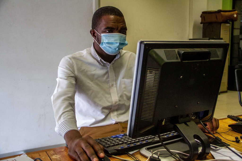 A man is seen working wearing a mask in his office during the lockdown on January 5, 2021 in Harare, Zimbabwe.