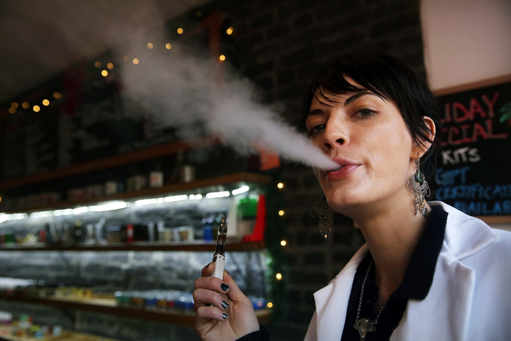 Catharine Candelario, an employee at the newly opened Henley Vaporium, vapes, or smokes an electronic cigarette, on December 19, 2013 in New York City.