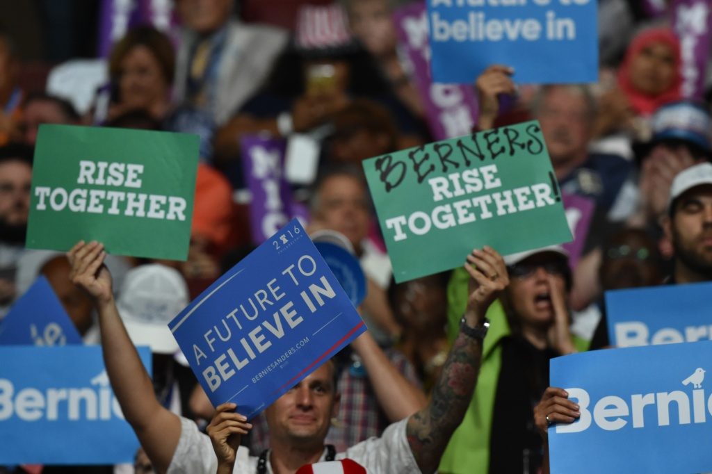 People holds signs during the 2016 Democratic National Convention July 25, 2016 in Philadelphia, Pennsylvania.