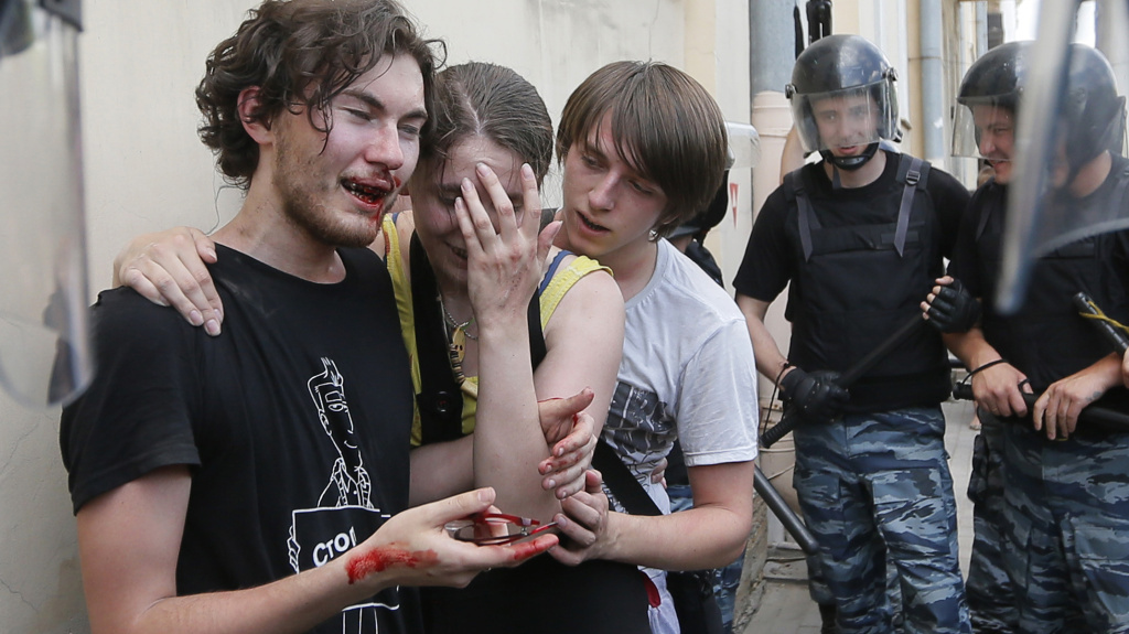 Riot police guard gay rights activists who have been beaten by anti-gay protesters during an authorized gay rights rally in St. Petersburg, Russia, on June 29. While a march there was allowed to go ahead, gay rights activists in Moscow turned to the Web on Sunday to celebrate gay pride.
