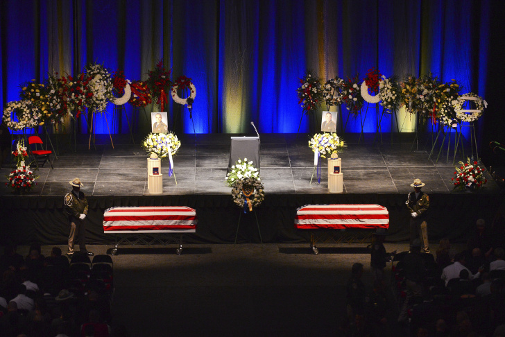 California State Troopers attend the caskets of two California Highway Patrol officers during a memorial ceremony at the Save Mart Center in Fresno, Calif., Monday, Feb. 24, 2014.  Brian Law and Juan Gonzalez , killed while responding to a crash south of Fresno, are being remembered Monday in a large ceremony that drew visitors from several states.