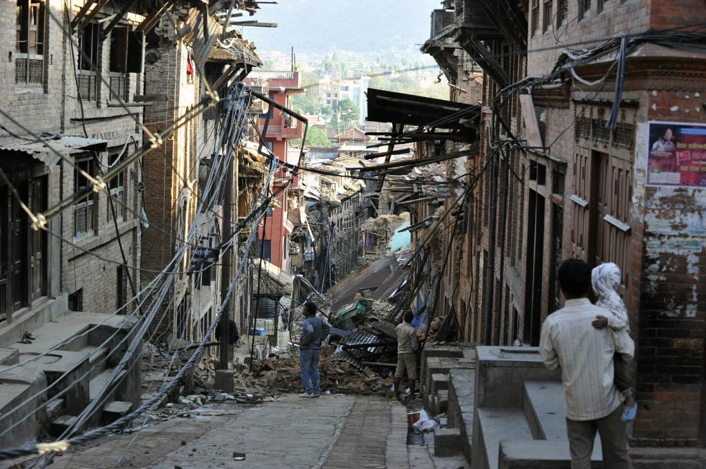 Residents look at collapsed houses in Bhaktapur, on the outskirts of Kathmandu, on April 27, 2015, two days after a 7.8 magnitude earthquake hit Nepal. Nepalis started fleeing their devastated capital on April 27 after an earthquake killed more than 3,800 people and toppled entire streets, as the United Nations prepared a